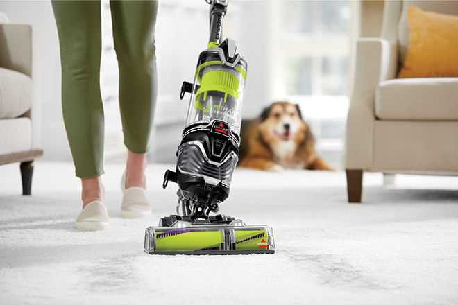 Woman vacuuming carpet with BISSELL's Pet Hair Vacuum